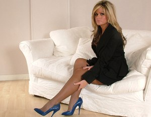 Fully clothed blonde flaunting her nice legs in sheer stockings and high heels