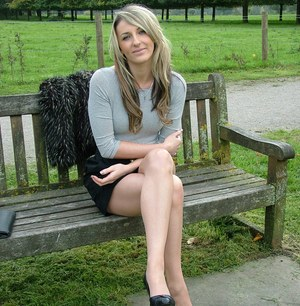 Leg model poses on a country bench in black skirt and pumps