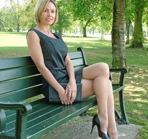 Clothed business woman shows off her sexy legs in high heels in the park