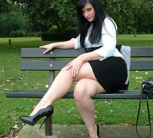 Clothed model Nicola poses on a park bench to show off her sexy legs