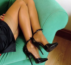Classy female with dark skin shows off her stiletto heels in nylons