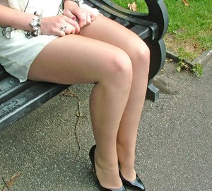 Thick woman in glasses shows off her stiletto heels on a park bench