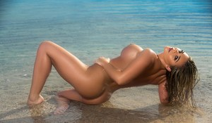Centerfold Tahlia Paris poses all sexy on the sand with her perfect tits bared