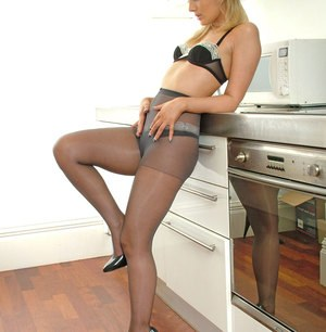 Lingerie model poses in the kitchen wearing pantyhose and black high heels