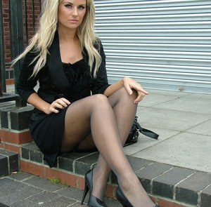 Erotic model in black dress flaunts her long legs in sheer pantyhose outside