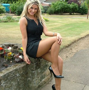Hot blonde shows off her great legs in a black dress and stiletto heels