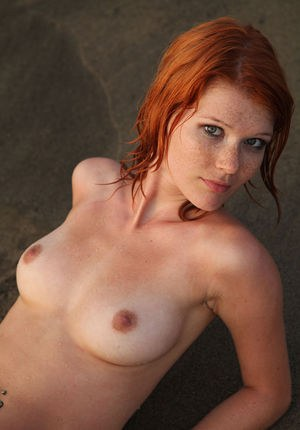 Hot redhead Mia Sollis playing naked in the sea and spreading legs on the sand