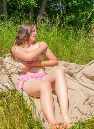 Sexy fatty with huge saggy tits disrobes to sunbathe naked in a field