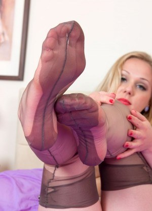 Aston Wilde shows off her nylon attired feet after partially disrobing on bed