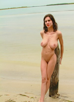 Brunette amateur reveals her huge boobs as she gets naked at the beach