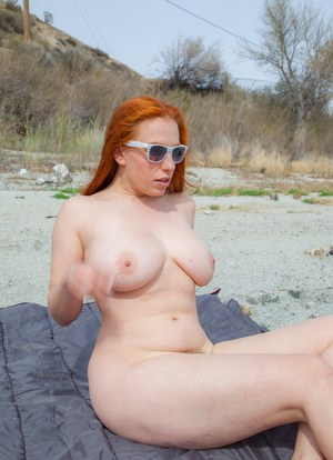 Mature redhead removing her bikini top at the beach to release her saggy tits