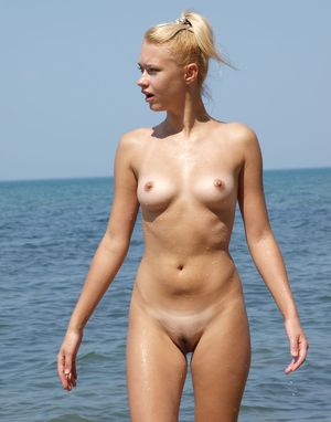 Graceful blonde beauty playing naked in the sand at the beach with wet ass