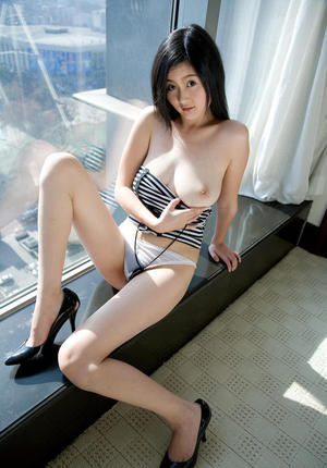 Young Asian Elva Tan shows her big tits in the window and bares her hairy twat