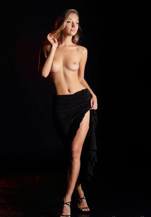 Gorgeous blonde model slips a long black dress over her perfect body