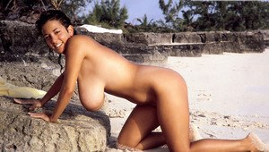 Busty MILF Devon Daniels gets her massive melons covered in sand at the beach