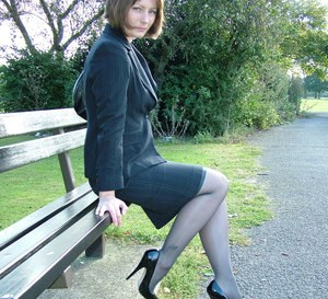 Pretty non nude woman in black stockings flaunting her heeled feet outdoors