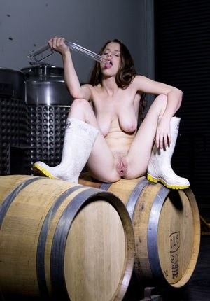 Naked Avri Norwood in rubber boots masturbating solo with dildo on beer kegs