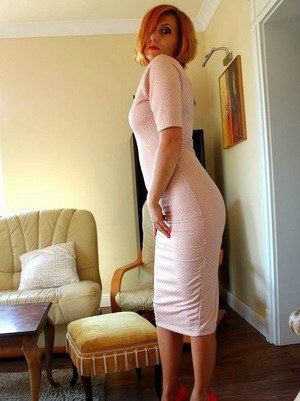 Sexy redhead Vixen Nylons strips her tan nylons and red pumps