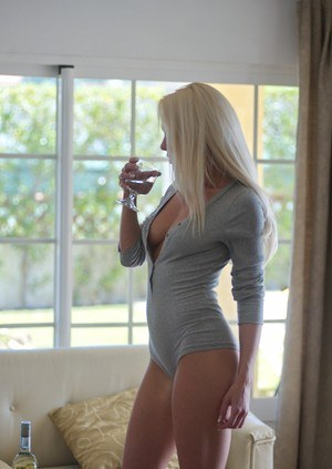Leggy blonde chick frees her tits from her onesie over a drink