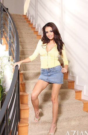Brunette solo model Daisy Marie takes off her skirt and panties on the stairs