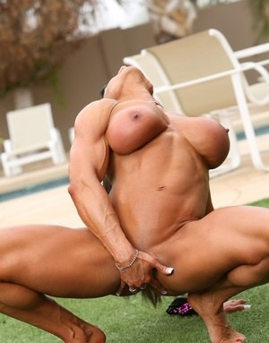 Female bodybuilder Marina Lopez poses in the nude on back lawn