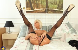 Sexy mature woman strips to her stockings to insert pleasure balls in her twat