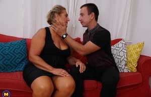 Mature housewife and her young boy toy fuck on a red chesterfield