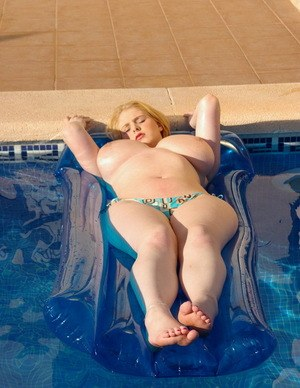 Ashley Sage Ellison fools around in the pool on her rubber lilo