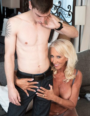 Hot blonde mature mom gets on her knees topless to pleasure her young boy toy