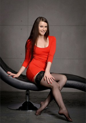 Comely brunette in short ed dress peels to pose nude with legs spread