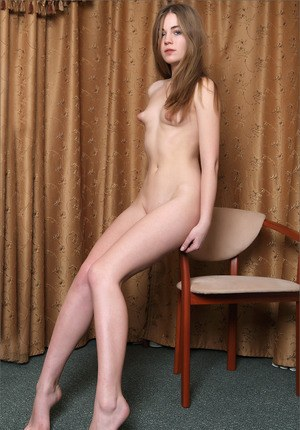 Young beauty with puffy nipples posing her skinny body naked on a chair