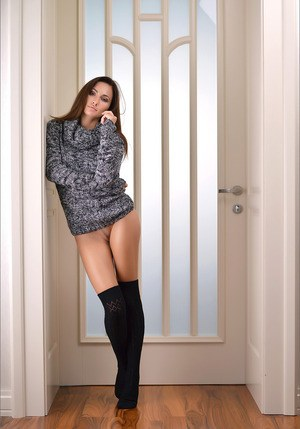 Erotic model undressing to pose naked with her long legs in knees socks
