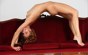 Thin redhead model shows off her long legs and bald twat in the nud
