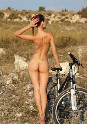 Skinny brunette bicyclist takes off her clothes and gloves to pose nude