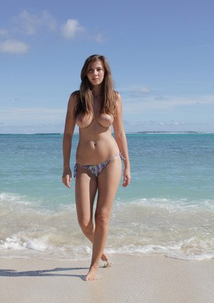 Solo girl and exhibitionist at heart poses naked on a sandy beach
