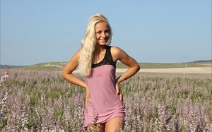 Smiling blonde slut loses her mini dress to romp naked in a field of flowers
