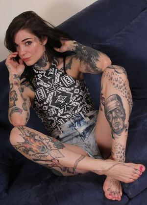 Tattooed female shows off the soles of her feet wearing jean shorts