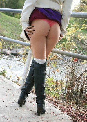 Slutty Madden in boots lifting her skirt outdoors to give a booty glimpse