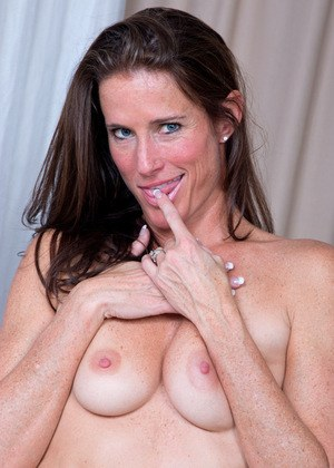 Older housewife Sofie Marie shows off her long legs before toying her snatch