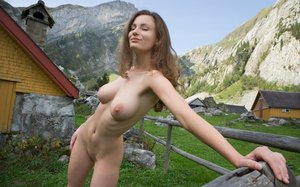 Buxom Susann lounges naked on a fence with nipples hard in the mountain air