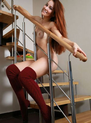 Pale redhead pose her thin body in shade appropriate over the knee socks