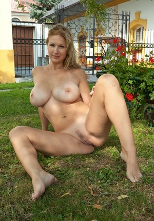 Buxom Karol on her knees naked in the yard letting her huge big tits hang