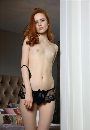 Beautiful redhead naked on the bed spreading her skinny legs to show pink
