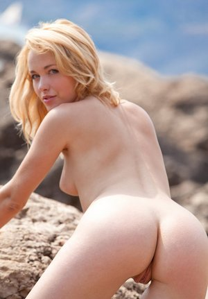 Naked blonde Tinna scrambles among the rocks showing hot bare ass at the beach