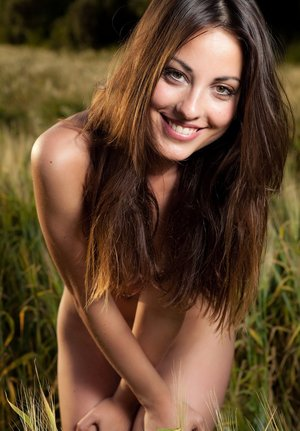 Thin brunette model Lorena G pulls off a cotton dress for nude poses in grass