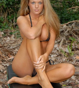 Natural blonde model with long hair removes her bikini top in the forest