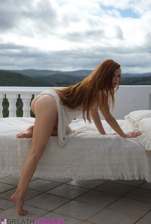 Pale redhead Mia Sollis slips out of a see thru dress to pose nude on balcony