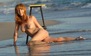 Gorgeous sexy redhead Birgid poses her hot body nude with a stool at the beach