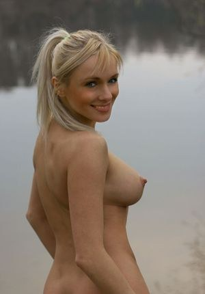 Hot blonde Yanina with natural big tits walks naked outdoors by the river