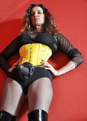 Older lady grabs her strapon while posing in fishnets boots and waist cincher